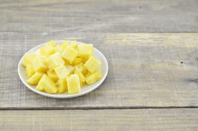 L'ananas fresco ha tagliato i cubi in piatto bianco sulla tavola di legno fotografia stock libera da diritti