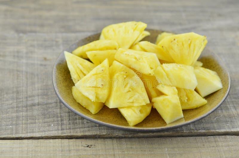 L'ananas fresco ha tagliato le fette in piatto marrone su fondo di legno fotografia stock libera da diritti