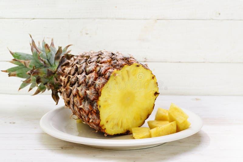 L'ananas organico affettato su un piatto, bianco ha dipinto il backgr di legno immagine stock