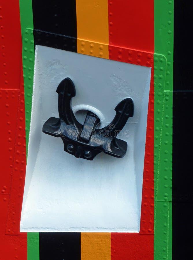L'ancre du bateau dans le renfoncement sur la coque rayée brillamment colorée photo libre de droits