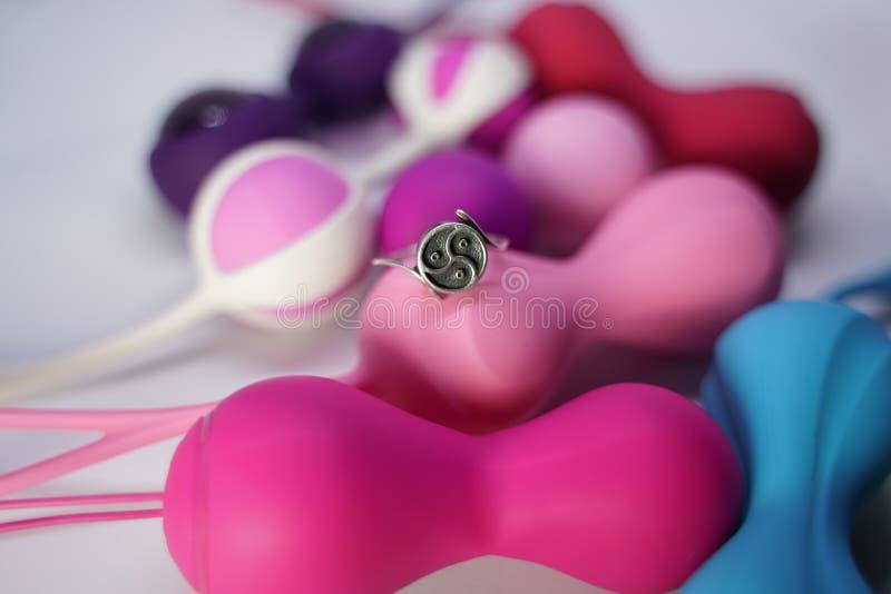 L'anello d'argento con il simbolo Triskel del bdsm si trova su un insieme delle palle vaginali dei giocattoli del sesso su un fon fotografia stock libera da diritti