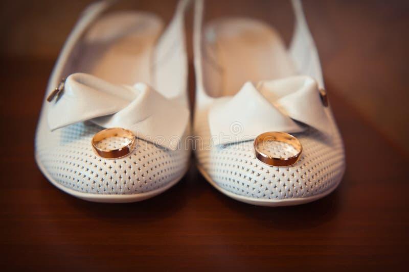 L'anello di oro sul bianco del ` s della sposa calza il primo piano immagine stock