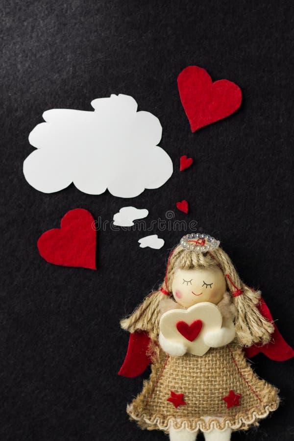 L'ange de fille de jouet tient une valentine dans des ses mains et pense à l'aimé photo stock
