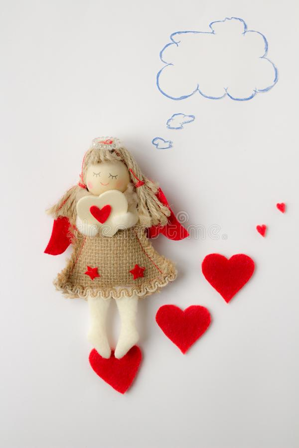 L'ange de fille de jouet tient une valentine dans des ses mains et pense à son amant sur un fond blanc photographie stock