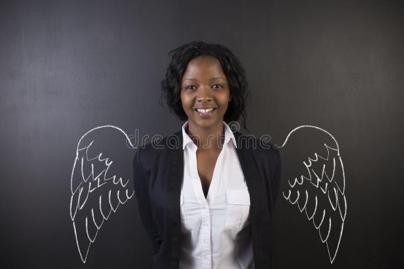 L'ange sud-africain ou d'Afro-américain de femme de professeur ou d'étudiante avec la craie s'envole photographie stock libre de droits
