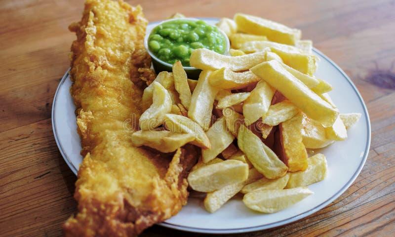 L'anglais a battu des poisson-frites de morue avec Mushy Peas dans un plat images libres de droits