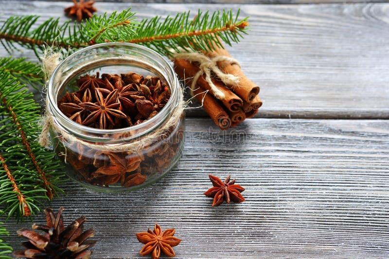 L'anice aromatico in barattolo con il pino si ramifica sui bordi immagine stock