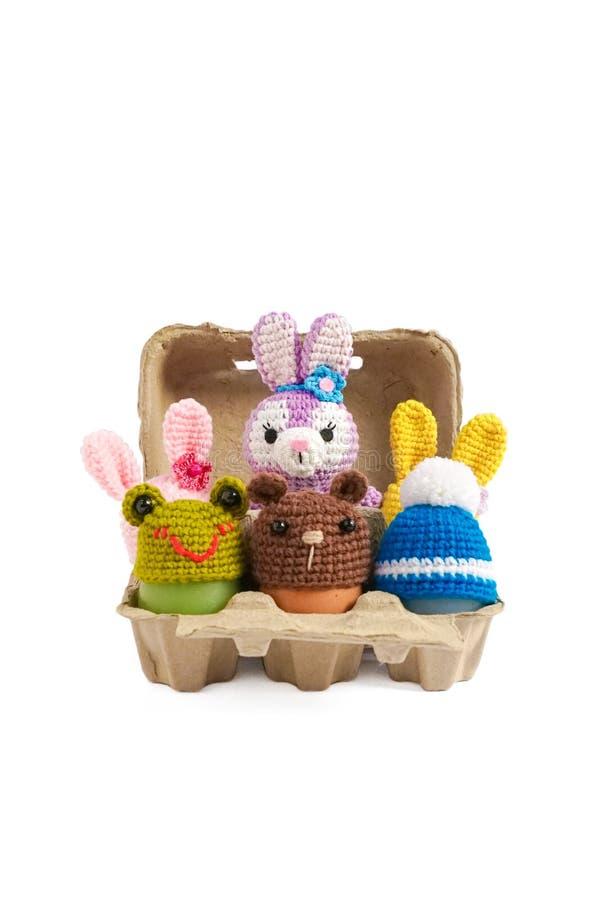 L'animale lavora all'uncinetto il cappello dell'uovo di Pasqua isolato su un fondo bianco E fotografia stock