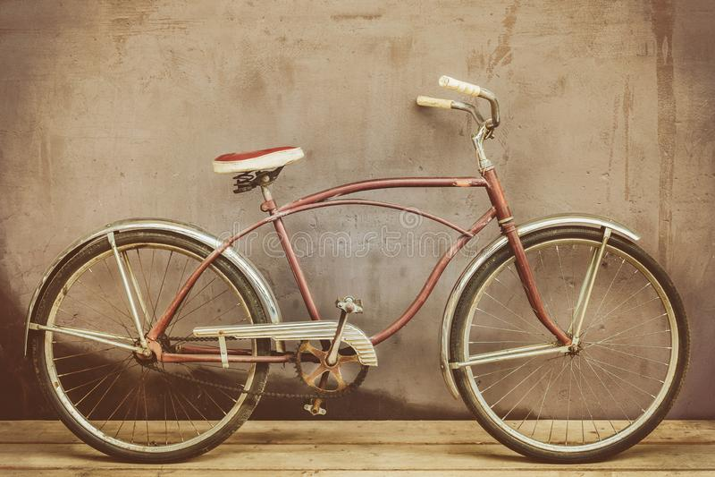 L'annata ha arrugginito bicicletta dell'incrociatore su un pavimento di legno fotografia stock libera da diritti