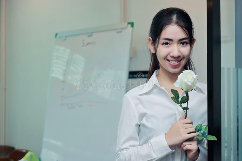 L'annata ha tonificato l'immagine di giovane donna asiatica attraente di affari tenendo le rose bianche in ufficio il giorno del  immagine stock