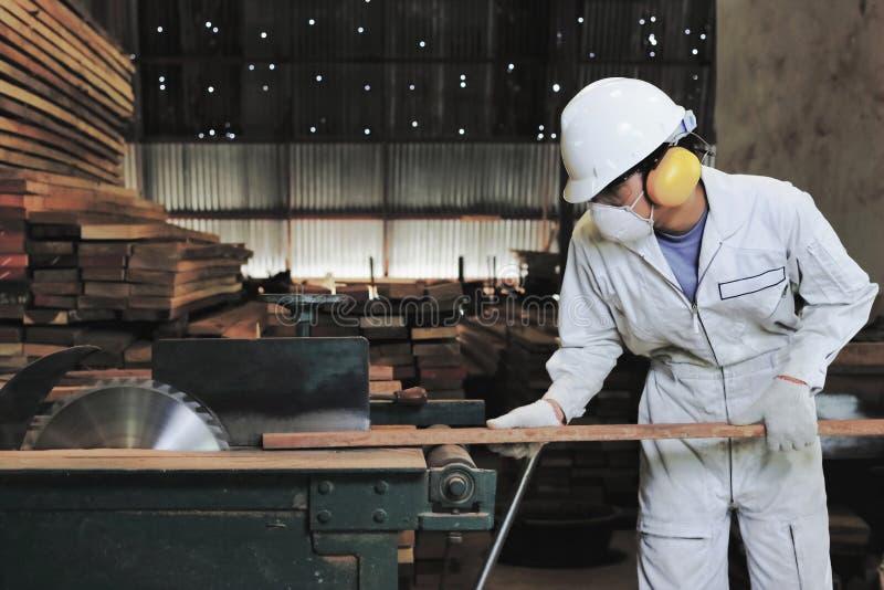 l'annata ha tonificato l'immagine Giovane carpentiere professionista con l'attrezzatura di sicurezza che taglia un pezzo di legno fotografia stock
