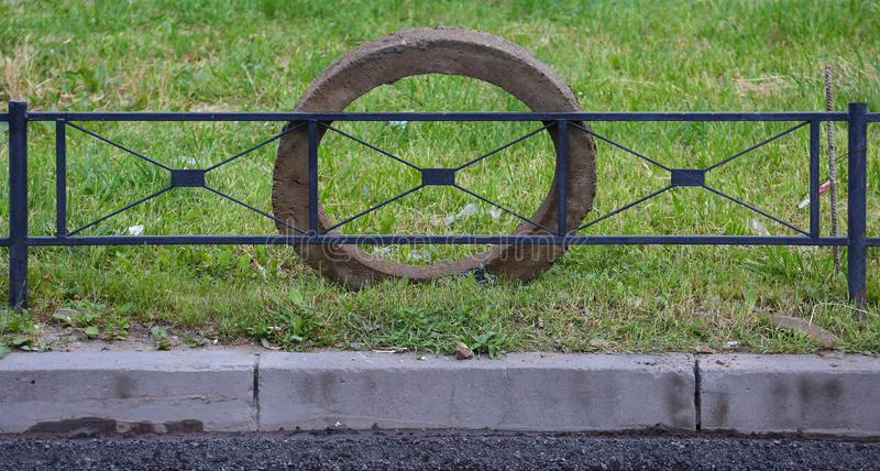 L'anneau concret gris s'élève à la barrière noire en métal de la pelouse verte photos stock