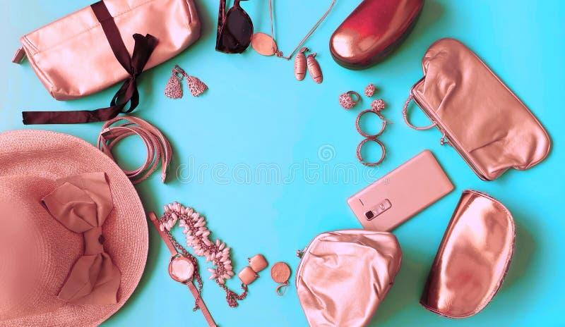 L'anneau de sunglass d'accessoires de femmes observe l'or rose de bourse d'arc de chapeau de mode cosmétique de bijoux sur le fon photographie stock