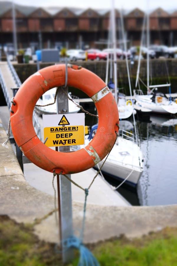 L'anneau orange rouge de balise de danger profond de risque de la vie de sécurité de l'eau sauvent la marina côtière de mer de po photographie stock