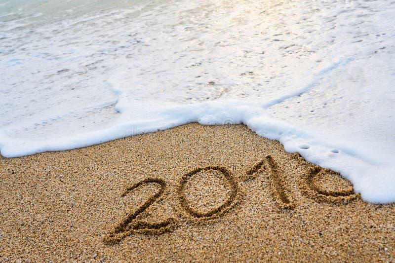 L'anno 2018 ha passato il concetto L'onda di schiuma lava via l'iscrizione 2018 scritta sulla sabbia fotografia stock libera da diritti