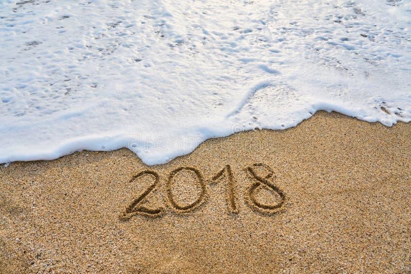 L'anno 2018 ha passato il concetto L'onda di schiuma lava via l'iscrizione 2018 scritta sulla sabbia immagini stock libere da diritti
