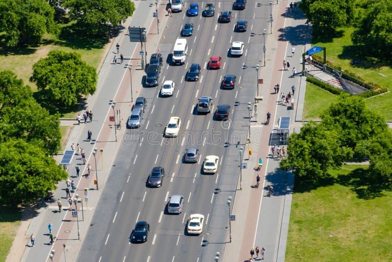 L'antenne de la rue passante et le trottoir trafiquent avec des voitures et des personnes image libre de droits