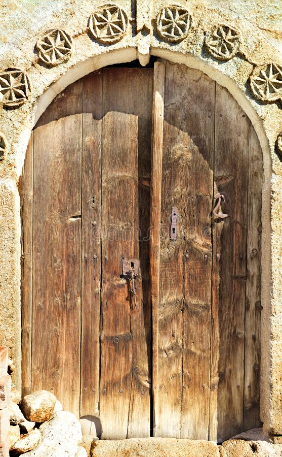 L'antiquité a arqué les portes en bois avec un modèle en pierre et une serrure en métal au milieu photo libre de droits