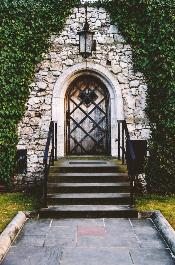 L'antiquité a arqué les portes en fer forgé dans un vieux mur en pierre de forteresse utilisant le lierre luxuriant vert Belle image libre de droits