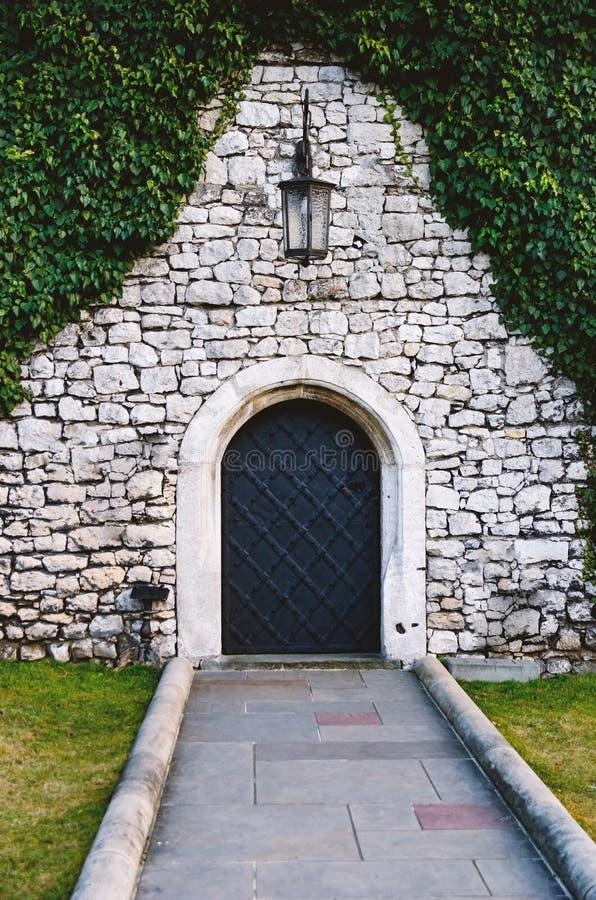 L'antiquité a arqué les portes en fer forgé dans un vieux mur en pierre de forteresse utilisant le lierre luxuriant vert Belle photo stock