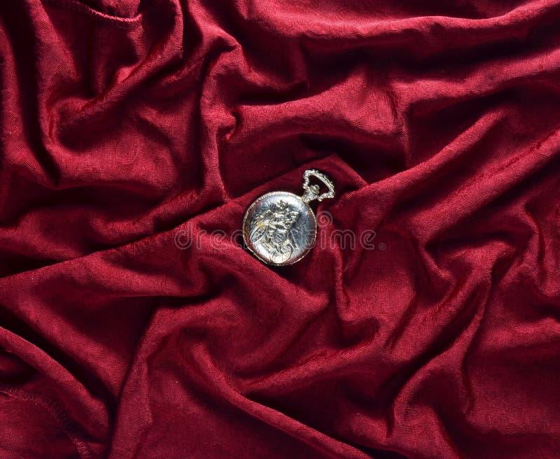 L'antiquité a fermé la montre de poche d'or sur un fond en soie rouge image stock