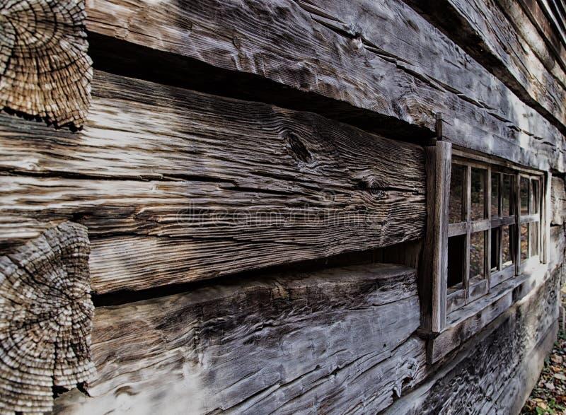 L'antiquité a survécu à la carlingue de rondin en dehors du mur et de la fenêtre photo libre de droits