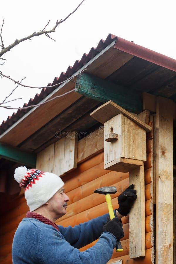 L'anziano anziano con i baffi attacca l'aviario al granaio immagini stock libere da diritti