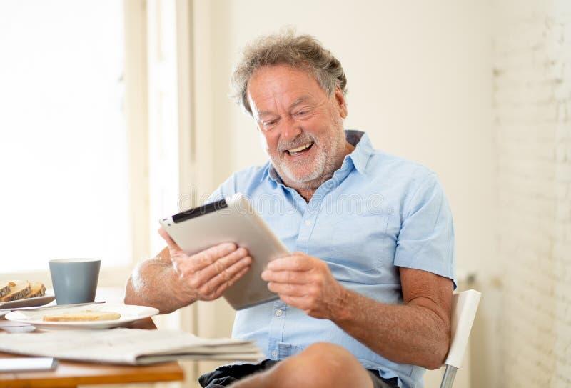 L'anziano bello si è ritirato l'uomo anziano che per mezzo della compressa con la gioia mentre mangiava la prima colazione a casa fotografie stock libere da diritti