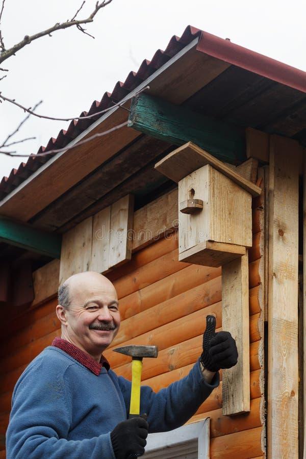L'anziano calvo con i baffi attacca l'aviario al granaio immagini stock