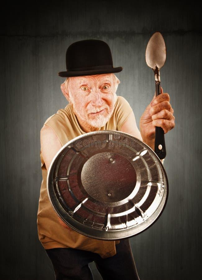 L'anziano che si difende con il cucchiaio e può coperchio fotografia stock libera da diritti