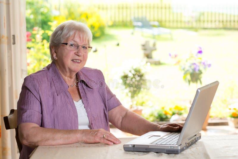 L'anziano femminile sta utilizzando il computer fotografie stock libere da diritti
