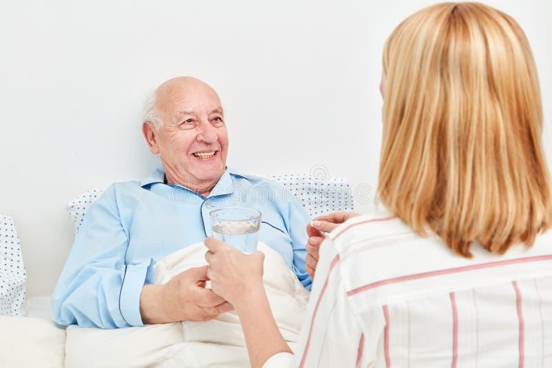 L'anziano malato a letto sta prendendo un farmaco immagine stock libera da diritti