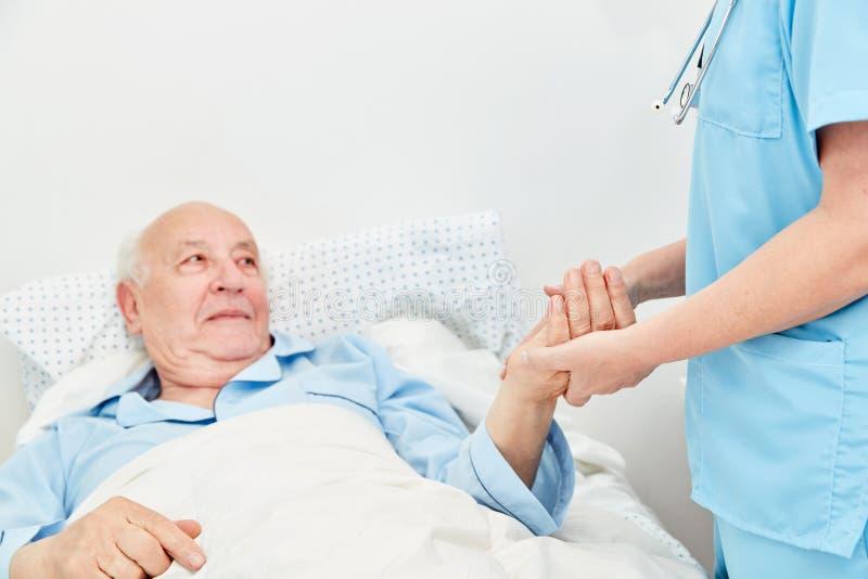 L'anziano malato sta trovandosi a letto nella casa di cura fotografie stock libere da diritti