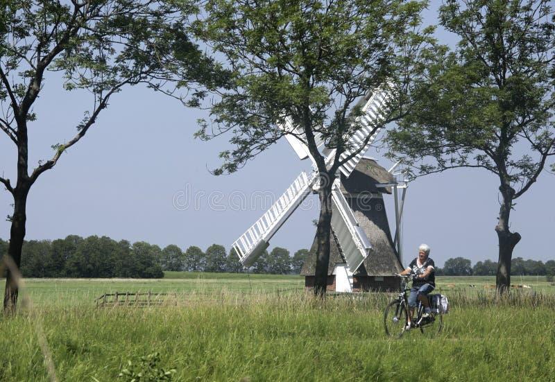 L'anziano olandese sulla bici passa un mulino a vento fotografia stock