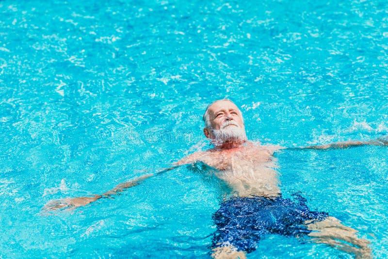 L'anziano sano godere di si rilassa il nuoto della piscina nella festa di vacanza da solo immagine stock libera da diritti