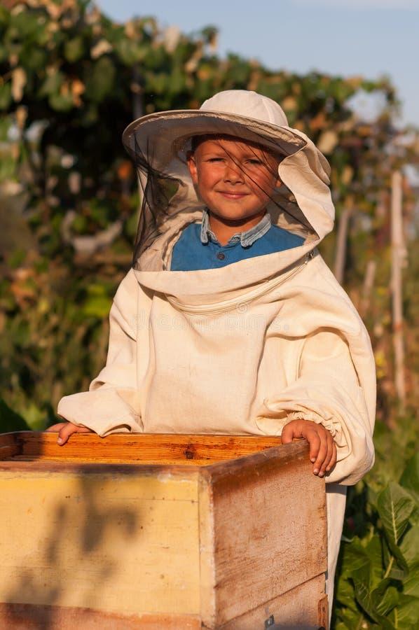 L'apiculteur de petit garçon travaille à un rucher à la ruche photo stock
