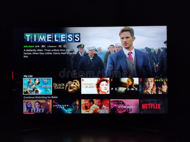 L'app Netflix sullo schermo televisivo che riproduce e il logo della serie `Timeless ` dietro fotografia stock libera da diritti