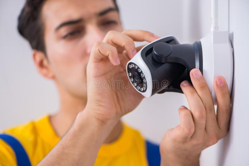 L'appaltatore che installa le macchine fotografiche del cctv di sorveglianza nell'ufficio immagini stock