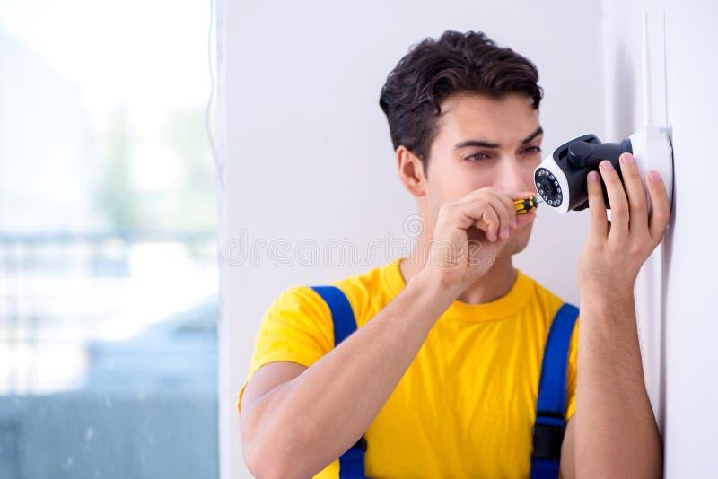 L'appaltatore che installa le macchine fotografiche del cctv di sorveglianza nell'ufficio immagini stock libere da diritti