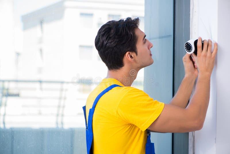 L'appaltatore che installa le macchine fotografiche del cctv di sorveglianza nell'ufficio fotografie stock libere da diritti