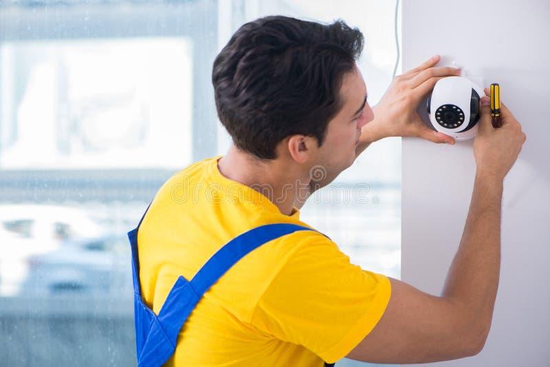 L'appaltatore che installa le macchine fotografiche del cctv di sorveglianza nell'ufficio fotografia stock
