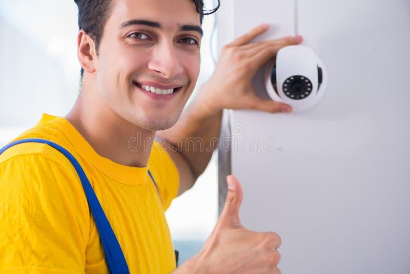 L'appaltatore che installa le macchine fotografiche del cctv di sorveglianza nell'ufficio immagine stock libera da diritti