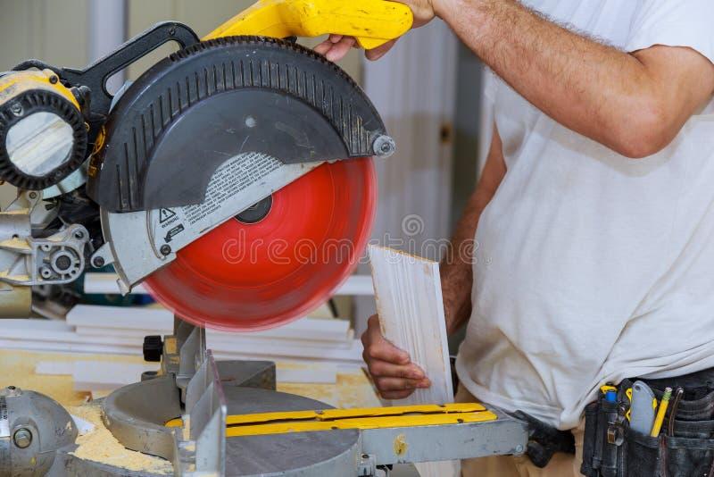 L'appaltatore che usando la circolare ha veduto il taglio del Baseboard nuovo per il rinnovamento fotografia stock