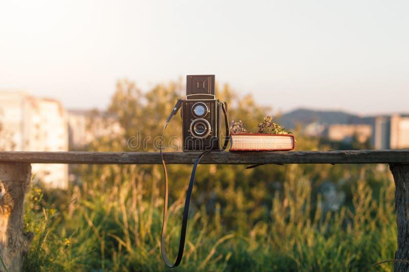 L'appareil-photo de film de vintage avec le livre et les fleurs sur le banc de parc derrière la ville verte aménagent en parc image libre de droits
