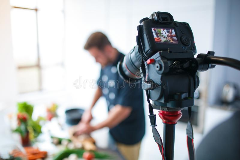 L'appareil-photo enlève le procédé de cuisson d'un homme photo stock