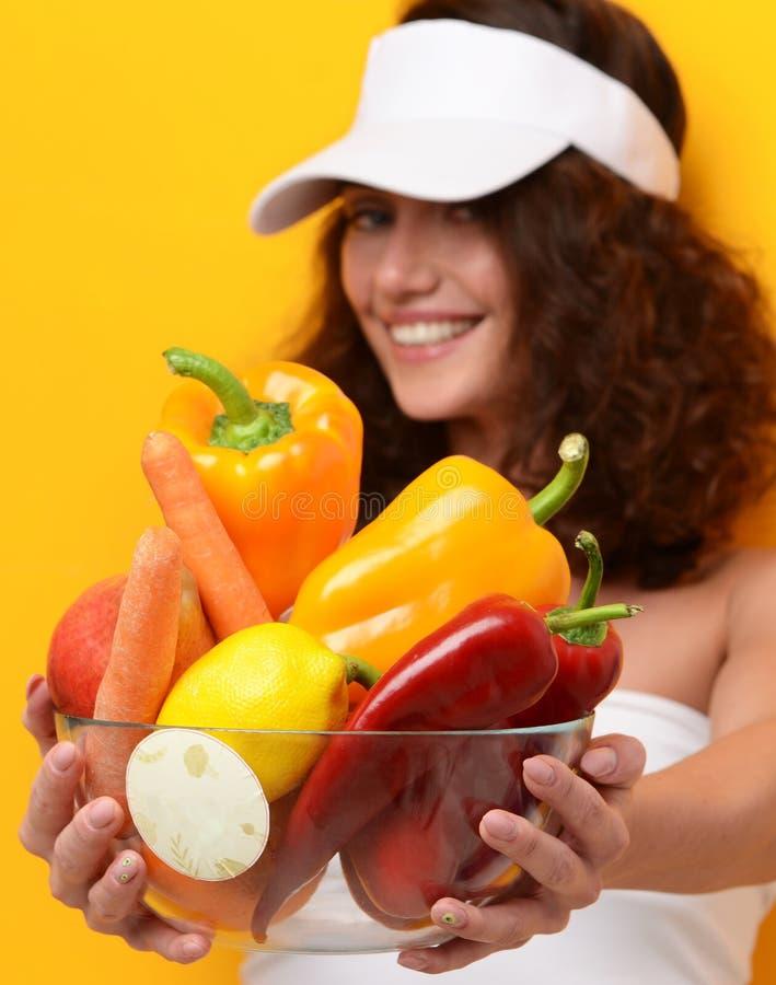 L'apparence de jeune femme donnent le plat d'épicerie complètement des légumes frais photos stock
