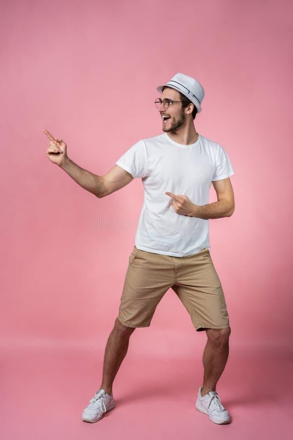 L'apparence de sourire attrayante de doigt de bras de jeune homme pour vider l'espace dans juste ont le signal de regard utilisan image libre de droits