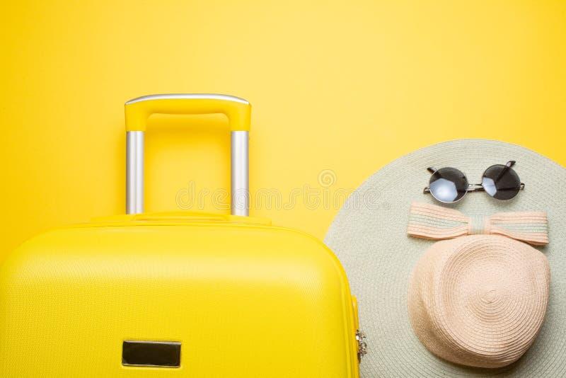 L'appartement étendent une valise jaune avec des accessoires pour détendre sur un fond jaune Concept de voyage, repos et détente image libre de droits