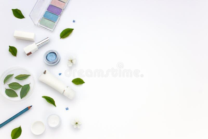 L'appartement blanc de cosmétiques étendent le cadre avec des fleurs et des feuilles Nettoyez le concept de beauté photos libres de droits