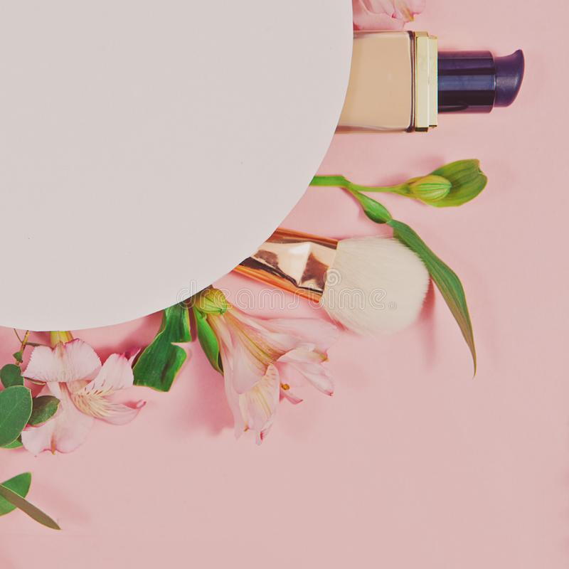 L'appartement décoratif étendent la composition avec des produits de maquillage, des cosmétiques et des fleurs Configuration plat photographie stock libre de droits